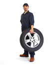 Car mechanic with a tire. Royalty Free Stock Photo