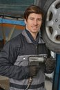 Car mechanic working under the smiling with pneumatic wrench Royalty Free Stock Image