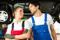 Car mechanics male and female in front of auto Stock Photography