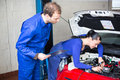 Car mechanics repairing car electrics other parts motor Royalty Free Stock Image