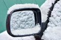 Car mirror covered with snow during snowing in winter time Royalty Free Stock Photos