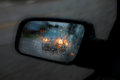 Car mirror in rain and traffic reflecting Royalty Free Stock Image