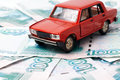 Car and money toy on the background of banknotes Stock Photos