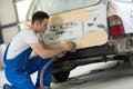 Car painter polishes body part Royalty Free Stock Photo