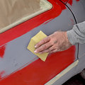 Car painting ready for repaint worker sanding primer Stock Photo