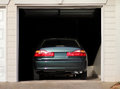 Car parked in a garage rear view of inside of residential Stock Image