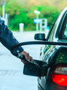 Car refuel fueling at the filling station holding a fuel pump male hand refilling with gas or petrol on outdoor Royalty Free Stock Images