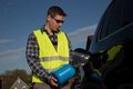 Car refuel on the road with a canister young man dressed an reflective vest is refueling his blue Stock Photo