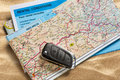 Car remote key on map and rental agreement Royalty Free Stock Photo