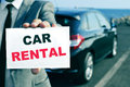Car rental a man in suit holding a signboard with the text written in it and a in the background Royalty Free Stock Image