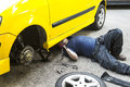 Car repairing a mechanic underneath a yellow doing maintain job Stock Photography