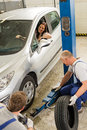 Car repairmen changing tire in garage caucasian salesman Stock Photo
