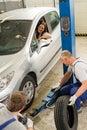 Car repairmen changing tire in garage Royalty Free Stock Photo
