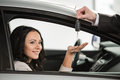 Car sales happy woman receives the keys to a new from a manager Royalty Free Stock Image