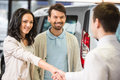 Car sales young couple grateful manager for advice in auto salon Stock Photos