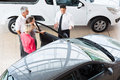 Car salesman customers overhead view of showing new vehicle to Stock Images