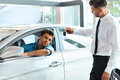 Car Salesman Handing over new Car Key to Customer at Showroom Royalty Free Stock Photo
