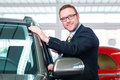 Car salesman selling auto to customer at dealership Stock Image