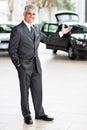 Car salesman welcoming friendly doing gesture at dealership Royalty Free Stock Photo