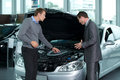 Car salesperson explaining about car s engine to customer Royalty Free Stock Photos