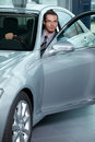 Car salesperson getting in car at showroom Royalty Free Stock Photography