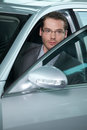 Car salesperson getting in car at showroom Royalty Free Stock Photo