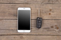 Car security concept - key with remote alarm control and smartphone Royalty Free Stock Photo