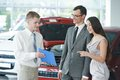 Car selling or automobile rental salesperson demonstrating new to young woman Stock Photography