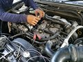 Car service engine, repair, check up maintenance, auto mechanic man tightened valve under hood car, people hand fixing car engine