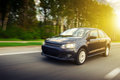 Fast drive car speed on the road at summertime sunset volkswagen polo sedan Royalty Free Stock Photo