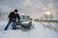 Car stuck in snow man digging up Royalty Free Stock Photography