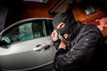 Car thief in a mask robber and the opens the door of the and hijacks the Royalty Free Stock Photos