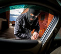 Car thief in a mask robber and the opens the door of the and hijacks the Stock Photo