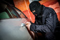 Car thief in a mask robber and the opens the door of the and hijacks the Stock Image
