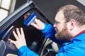 Car tinting. Automobile mechanic technician applying foil