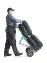 Car tire serviceman carrying a set of four new tires using hand truck shot on white Royalty Free Stock Images
