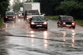 Car traffic on road when heavy rain drops in concrete Royalty Free Stock Photo