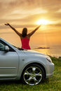 Car traveler looking summer sunset free woman on travel and ocean female driver leaning on bonnet raising arms to glow dusk sun Royalty Free Stock Photo