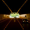Car tunnel cars on road in a with lights overhead Stock Photography