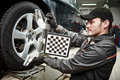 Car wheel alignment service work mechanic installing sensor during suspension adjustment and automobile at repair station Stock Image