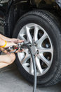 Car wheel changing replacing lug nuts by hand while tires on a vehicle Stock Image
