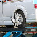 Car wheel fixed with computerized wheel alignment machine clamp Stock Image