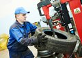 Car wheel tyre fitting or replacement auto repairman loading automobile at machine during tire replacing Stock Image