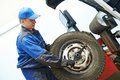 Car wheel tyre fitting or replacement auto repairman loading automobile at machine during tire replacing Stock Photos