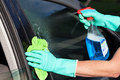 Car window washing a man a s using a rag and a spray Royalty Free Stock Photography