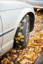 Car winter tire in autumn with with leaves scene low angle Stock Photo
