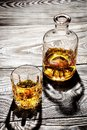 Carafe and a glass of aged cognac on a wooden table top shot Royalty Free Stock Photos