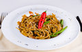 Carbohydrate rich tasty main course serving of noodles garnished with red pepper and beans in simple plating design Stock Photos