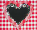 Card blank in heart shape with confetti on red gingham tablecloth winter holidays concept copy space for your text Royalty Free Stock Image