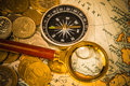Card with coins compass and magnifying glass gold color on the old map Stock Image